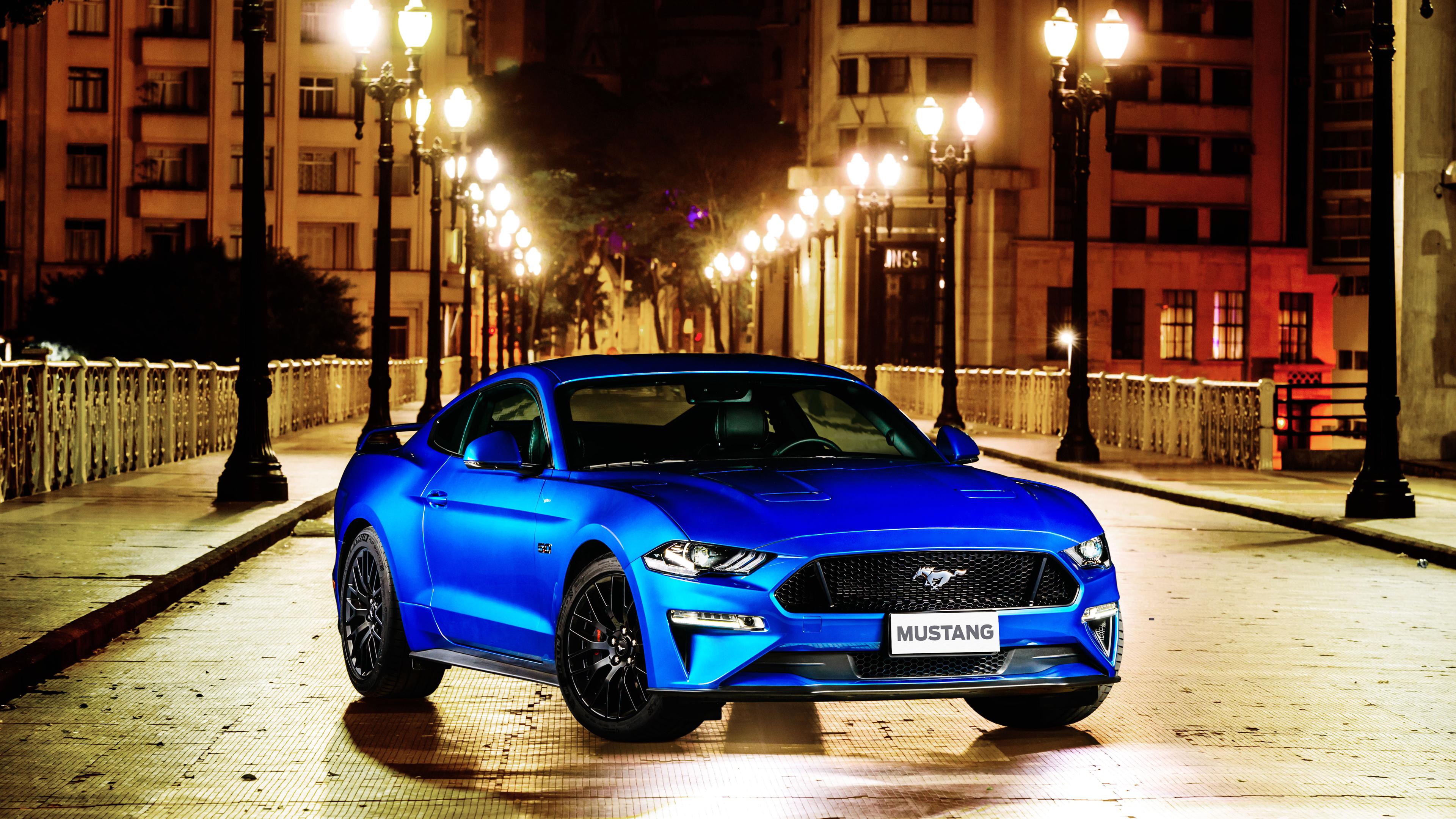 Ярко-синий автомобиль с эмблемой Мустанг в отблесках фонарей ночного города