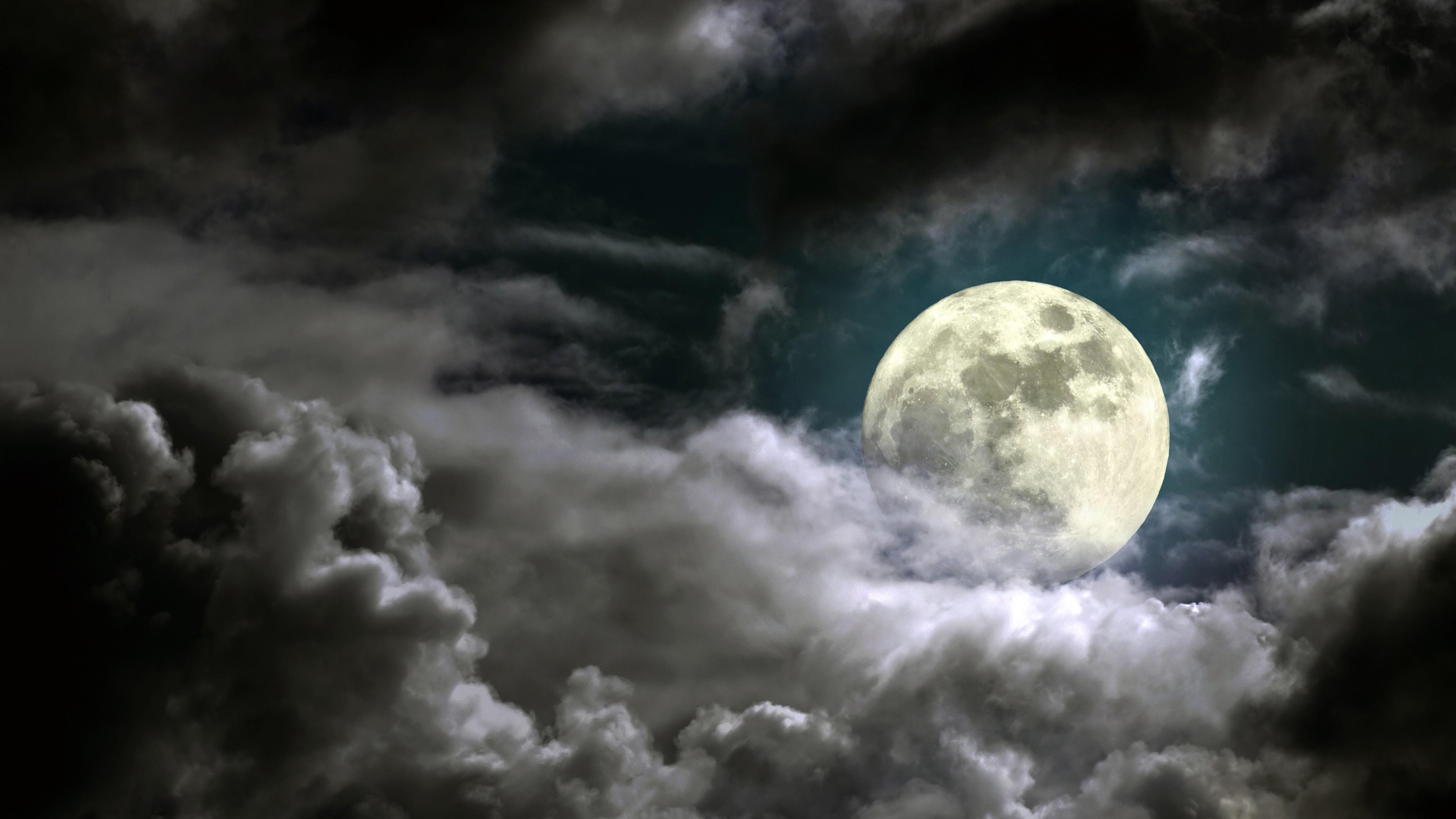 Луна в серо-дымчатых газовых облаках ночного неба