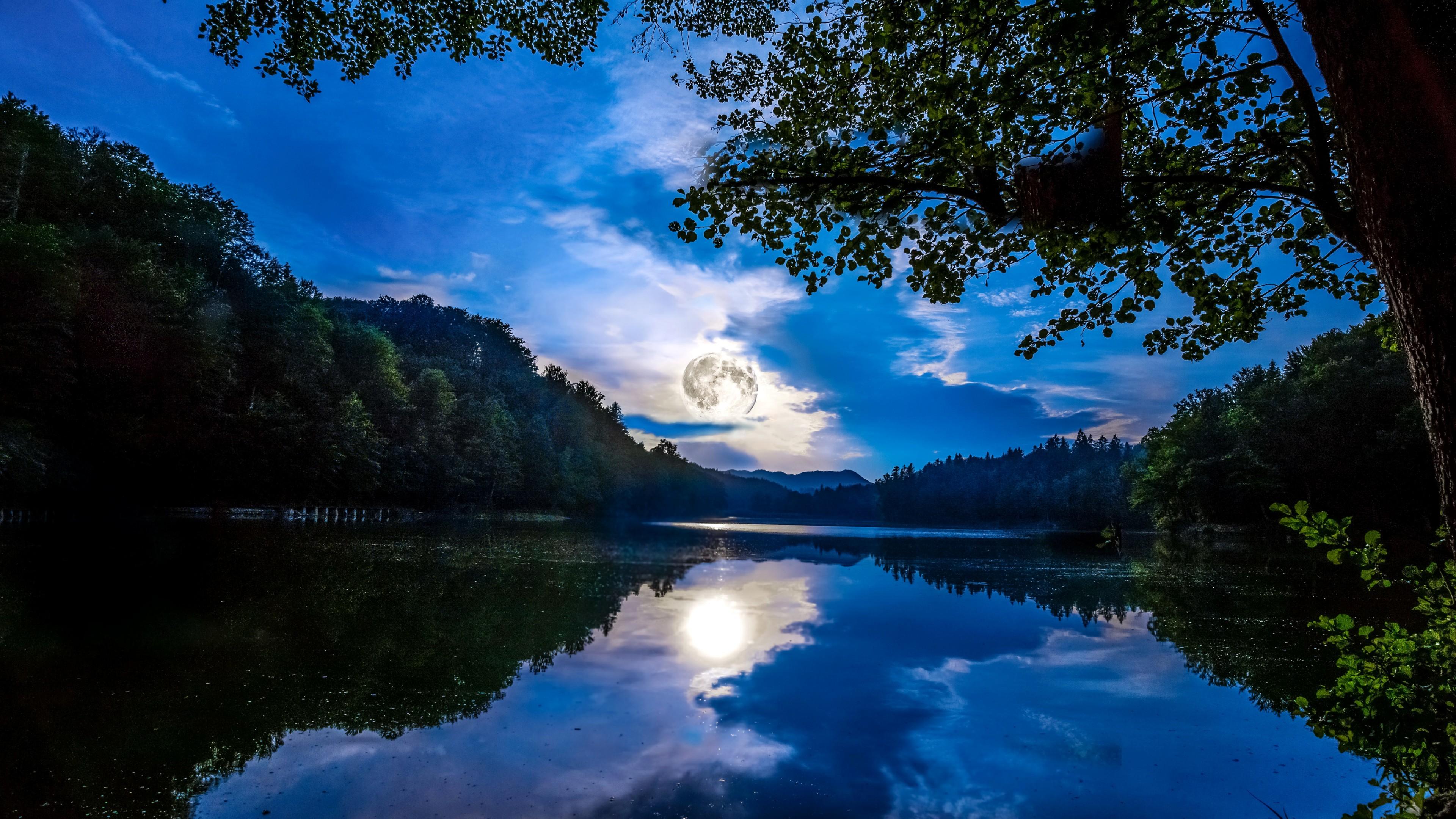 Отражение светящего шара луны и темно-синих облаков в зеркальной глади озера