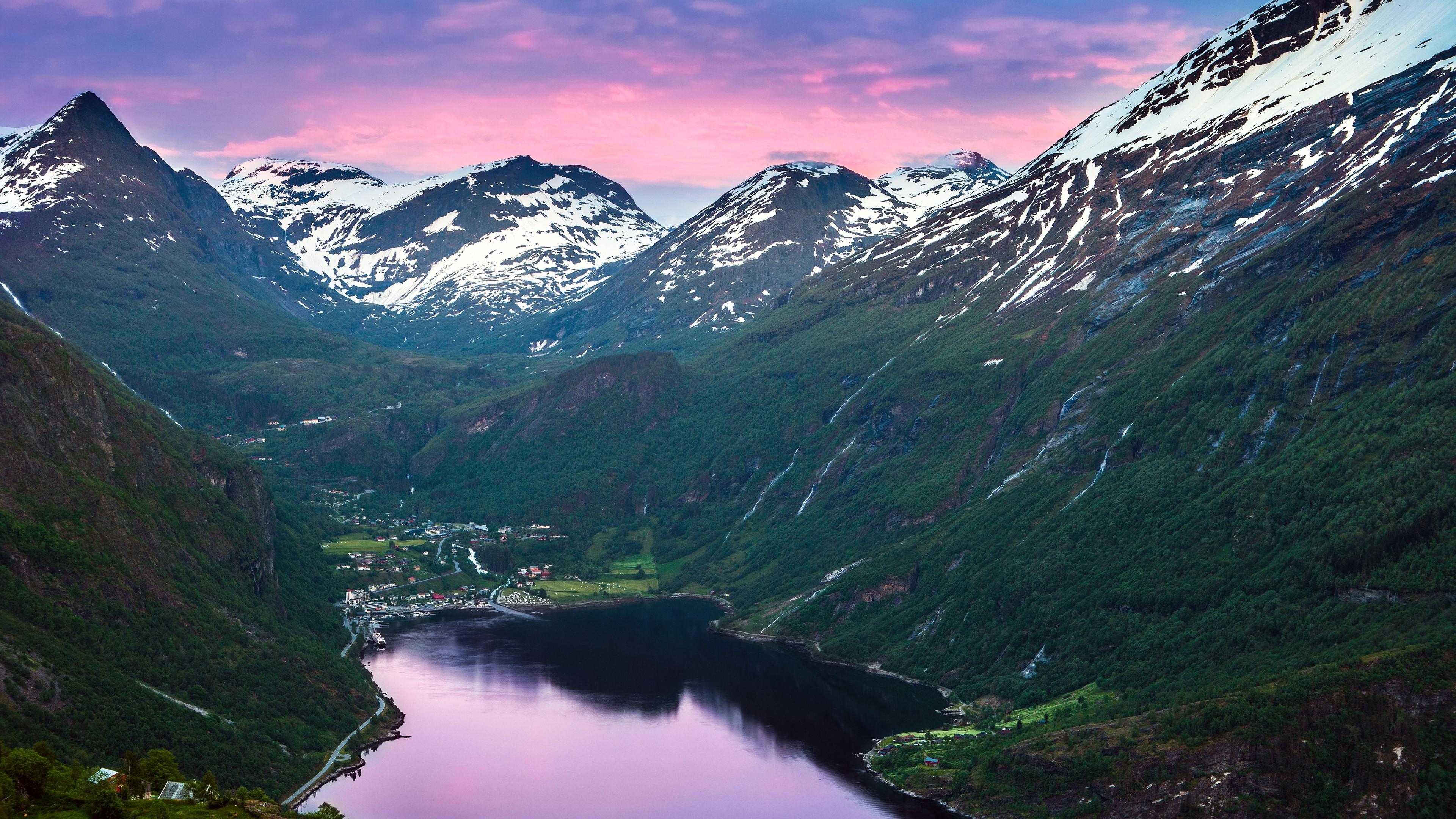 Горное озеро среди снежных горных вершин и изумрудной зеленью склонов