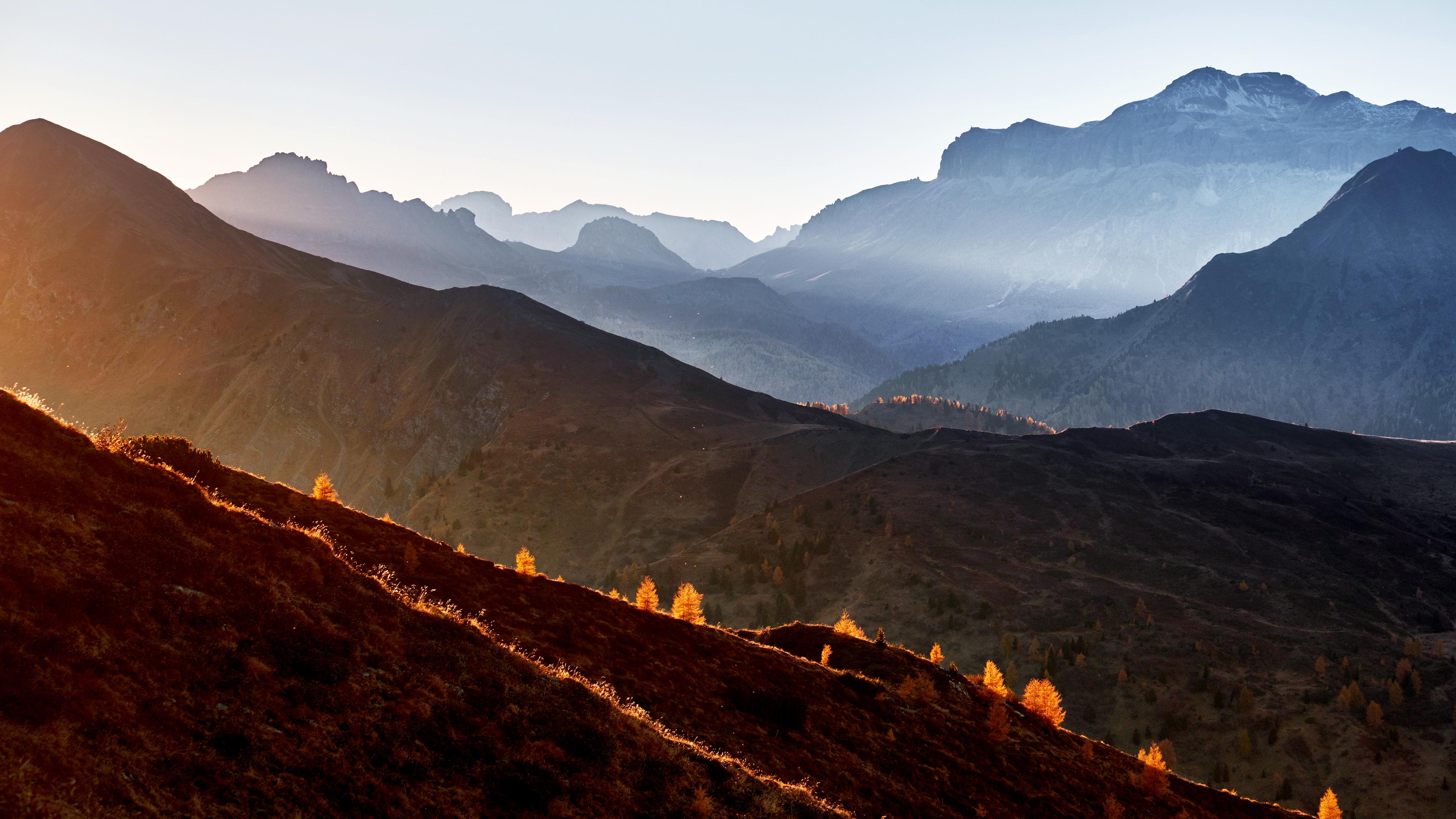 Склоны горных вершин окутаны утренним туманом и яркими лучами солнца