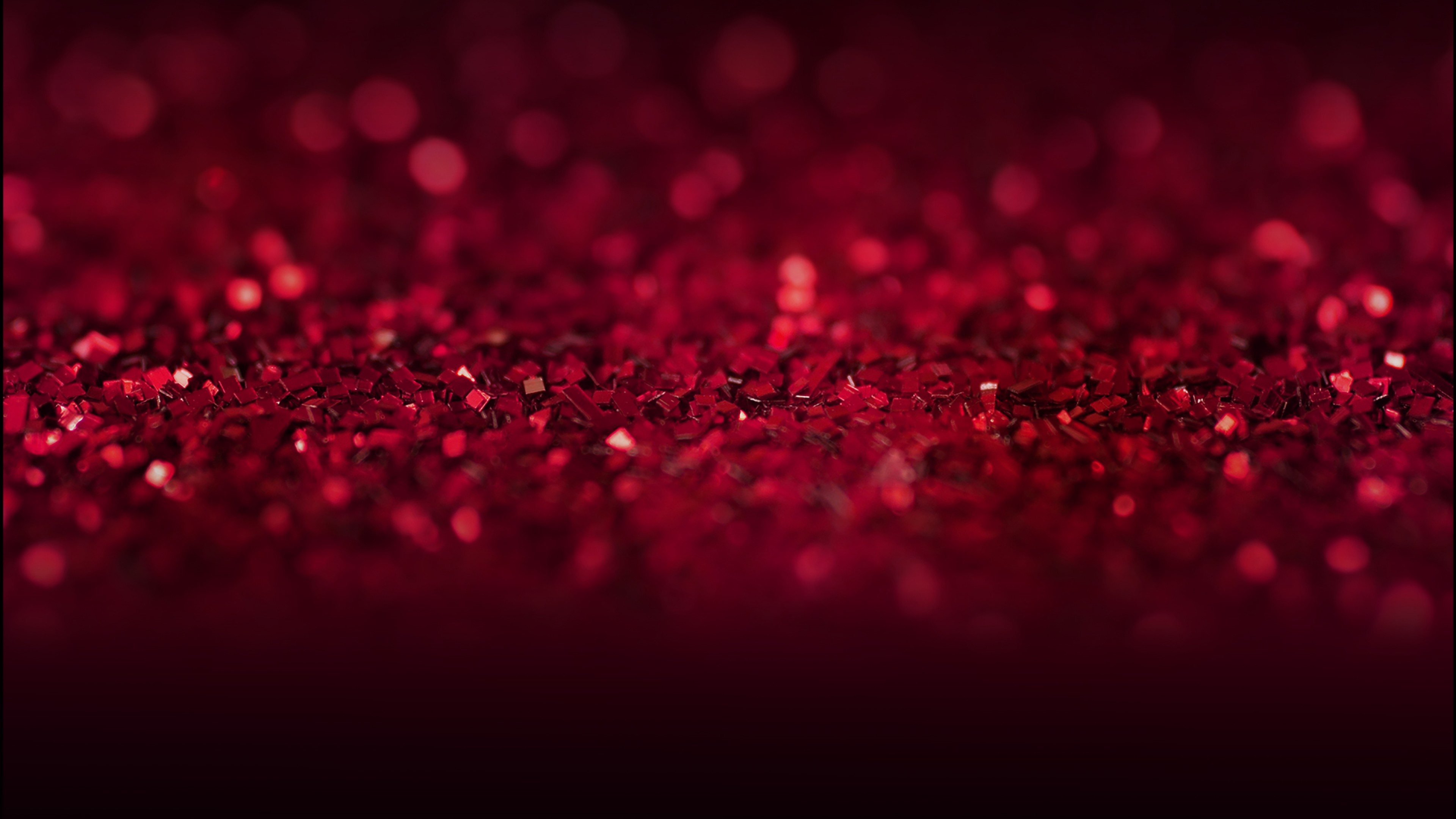 Розовые блестящие и красные камни на черном фоне