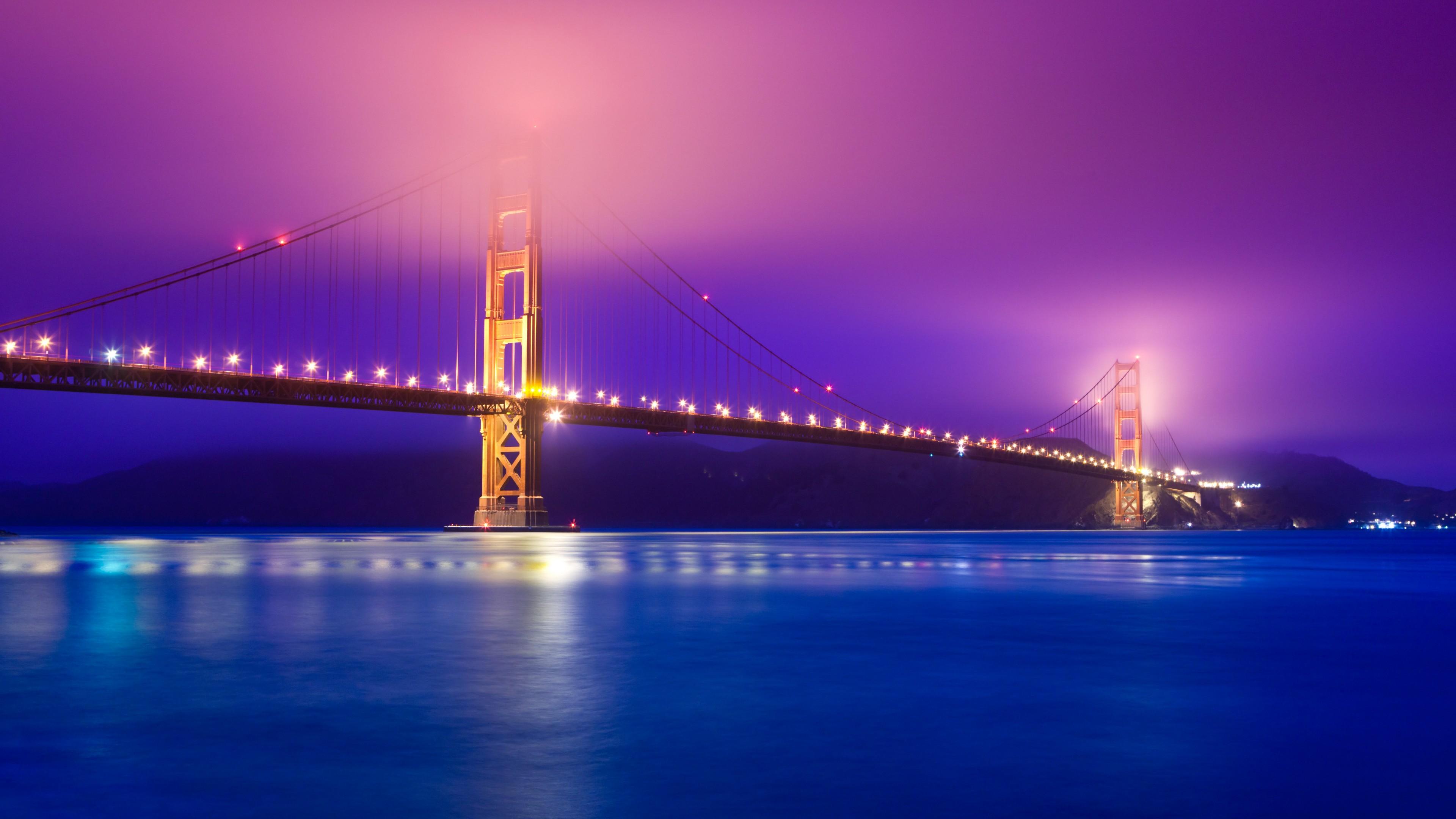 Розовый закат солнца над мостом Золотые ворота с отблеском огней, отражающих в заливе
