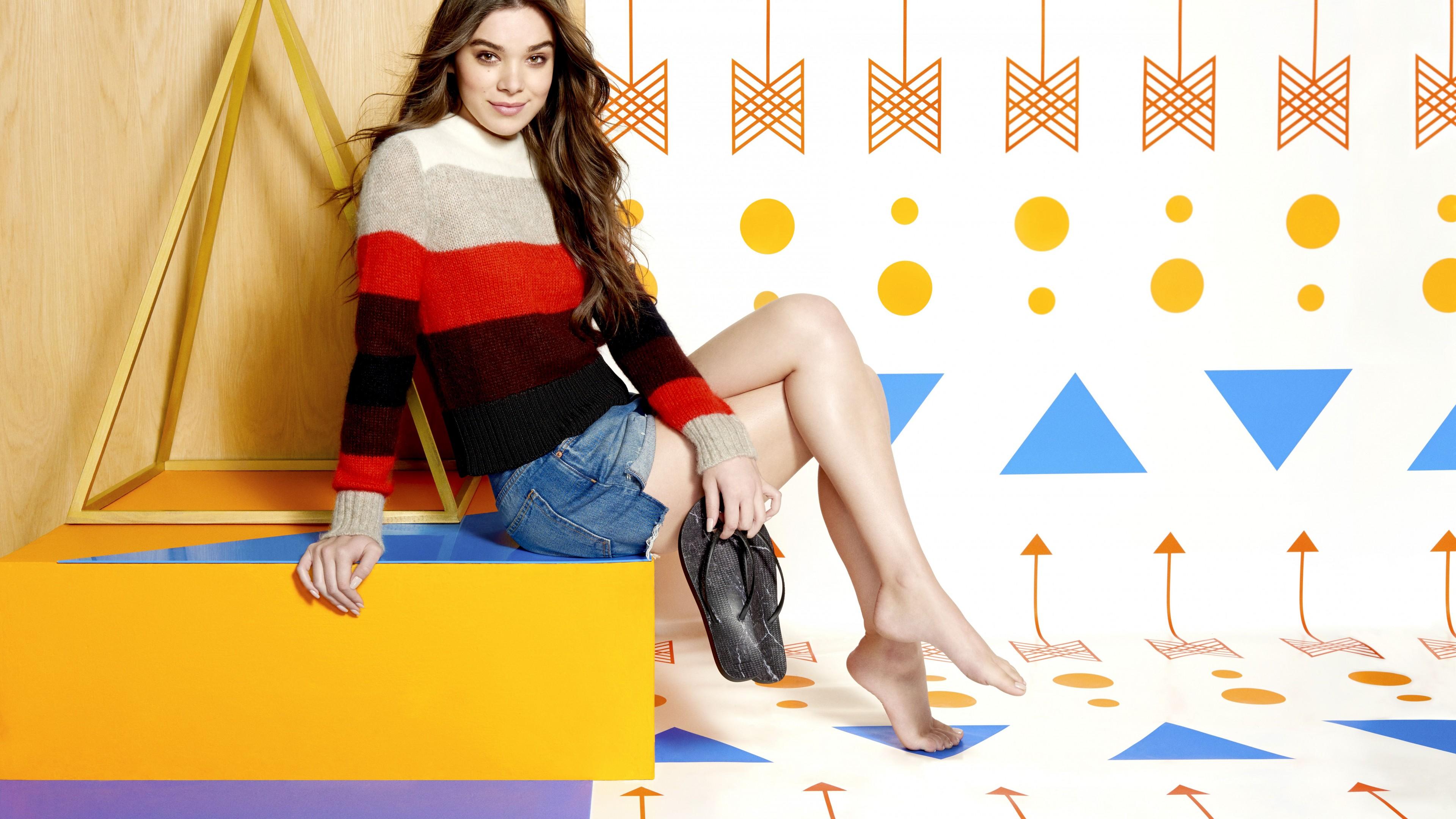 Брюнетка в свитере и шортах на фоне геометрических фигур