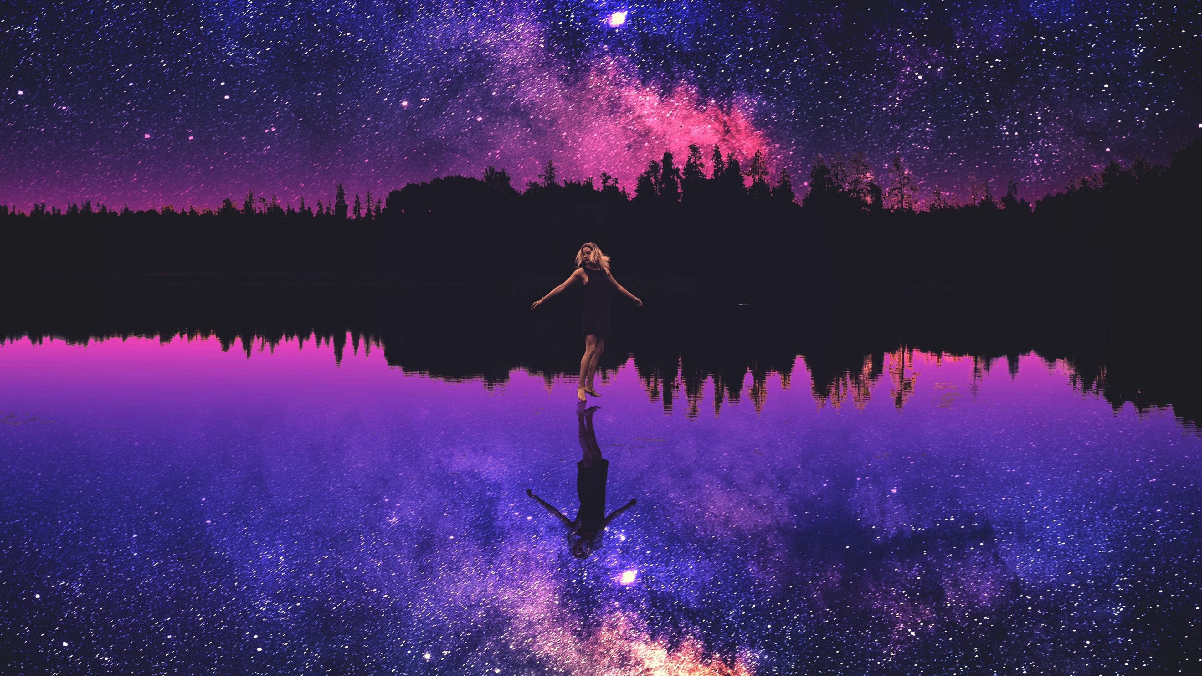 Силуэт девушки на фоне волшебного  небосвода с отражением золотой россыпи звезд